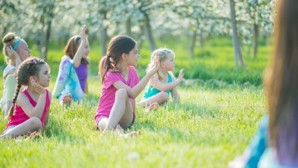 Kinder Yoga auf einer Wiese
